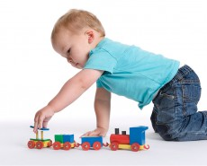 baby playing with toy train