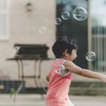 child playing in bubbles
